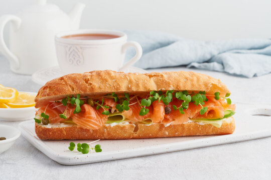 Big sandwiche with salmon, cream cheese, cucumber slices on white concrete table. Morning healthy breakfast with fish and cup of drink, side view, close up
