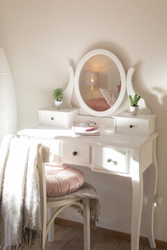 Detail of makeup dressing table with large mirror, diary and organizer. White and clean workstation in the master bedroom