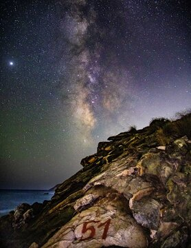 Playa rocosa con cielo despejado donde se puede ver la vía láctea claramente