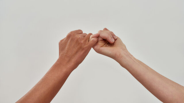 Close up of two hands hook little finger together to promise or asking for asking for reconciliation isolated over light background
