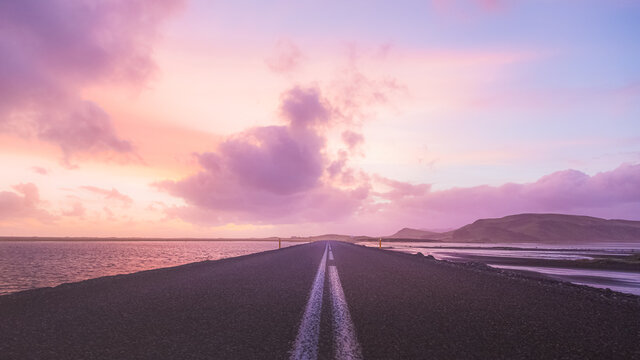 An empty road straight ahead near Dyrholaey in Southern Iceland with a colourful sunset.