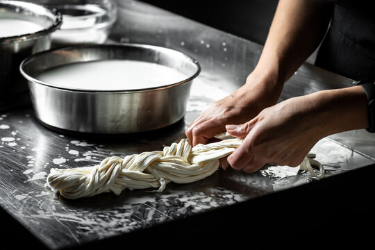 Production process of mozzarella cheese. woman working in a small family creamery is processing the final steps of making a cheese. Traditional Italian mozzarella