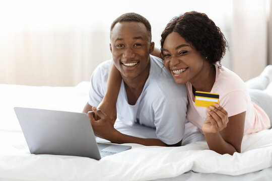 Young black couple laying on bed with laptop, shopping online