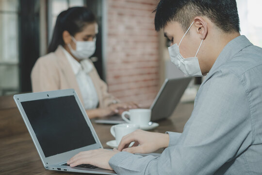 Businesswoman, businessman or employee young wearing face mark after back at work in office, workplace after lockdown with colleague. Business people, coworker, team  while working in room office.