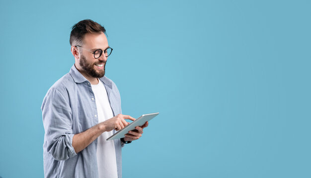Smart millennial guy in glasses using tablet computer over blue studio background, banner design with copy space