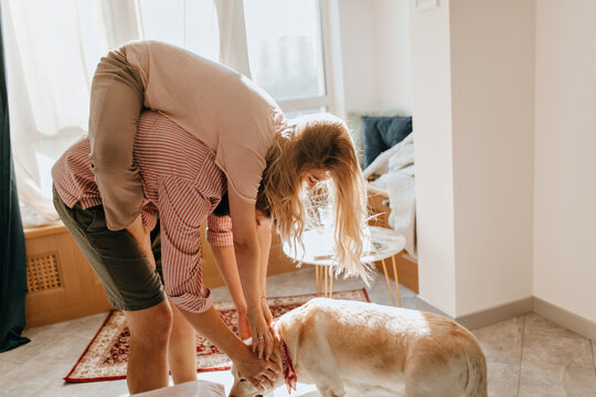 Couple is having fun and playing with their cute Labrador in living room. Girl in pajamas hung on her boyfriend like monkey