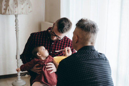 Male gay couple with adopted baby girl at home - Two handsome dads feed the baby girl on kitchen - Male babysitters - Lgbt family at home - Diversity concept