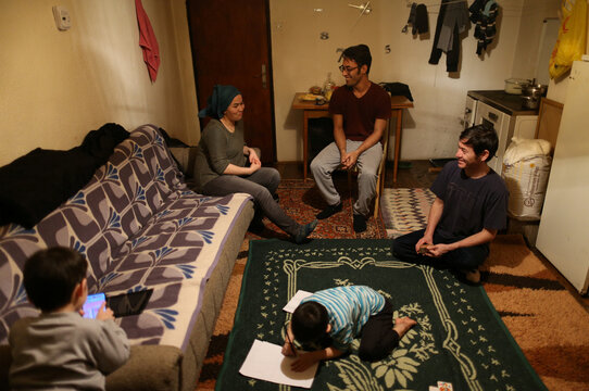 A couple from Iraq Nurziye and her husband Liaqat meet with her brother Hojjat at a temporary home in the village near Velika Kladusa