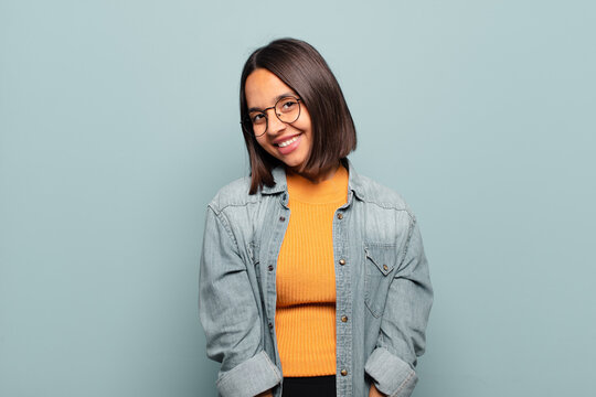 young hispanic woman smiling cheerfully and casually with a positive, happy, confident and relaxed expression