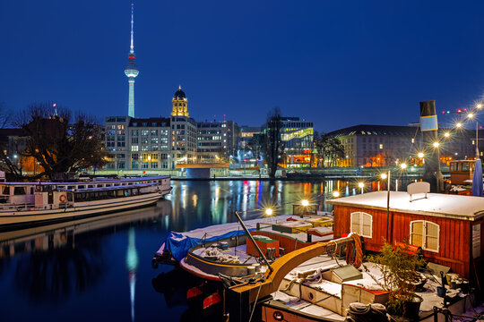 Illuminated Berlin at winter night against the Spree river, historical harbor in the downtown with old boats