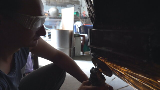 Mechanic polishing auto with electric tool at garage or workshop. Skillful mechanic restoring automobile. Bright sparks from polishing machine flying in dark garage. Repairman engaged servicing car