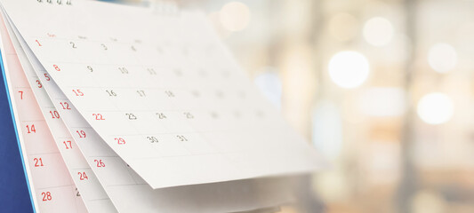 Obraz Close up white paper desk calendar with blurred bokeh background appointment and business meeting concept - fototapety do salonu