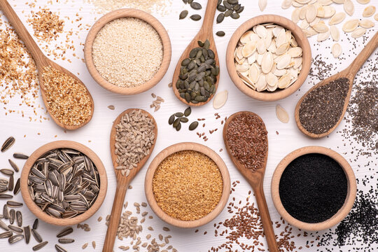 Healthy seeds - sesame, flax seed, sunflower seeds, pumpkin seed, chia and black seed in wooden spoons on a white background. Top view