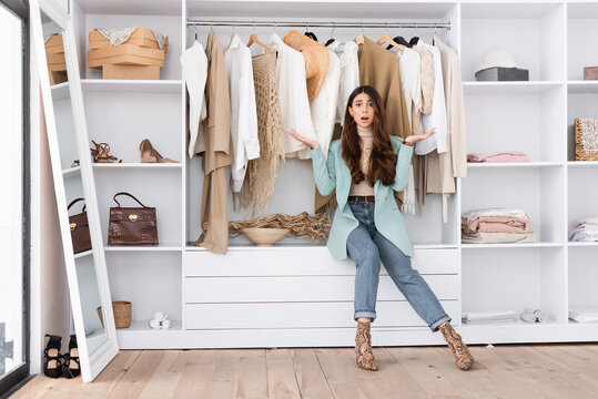 Worried woman pointing with hands in wardrobe