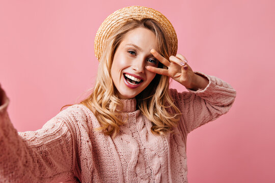 Lovely girl with natural make up is smiling and showing peace sign. Woman in straw hat and knitted sweater posing on isolated background