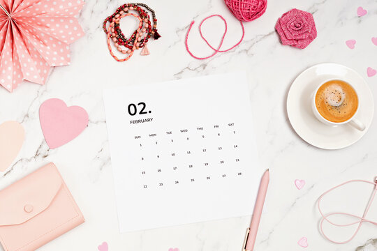 Desktop with calendar for february and pink accessories. home office, social media blog, schedule, planning concept. Flatlay, top view