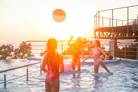Children resting in swimming pool together. Kids swim, dive, leisure and playing infatable ball in pool at suumer vacation against the sun