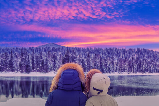 Hiker girls in down jackets standing near river against winter forest and amazing colorful sunset. Travel concept.