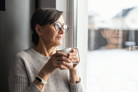 Close-up portrait of senior older woman wearing glasses enjoys morning coffee in the kitchen at home. A modern retirement lady daydreaming with a mug of hot drink looks through the window