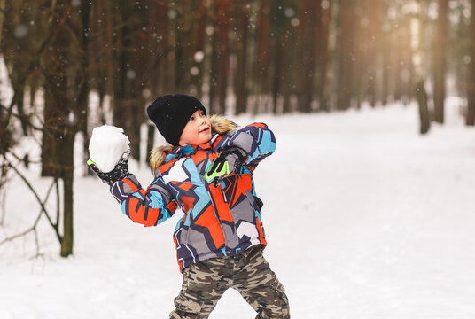 Little boy throws a snowball. Playing snowballs in winter in the park