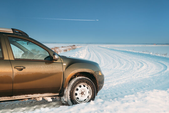 Car Renault Duster Or Dacia Duster Suv Parked On Winter Snowy Field Countryside Landscape. Duster Produced Jointly By French Manufacturer Renault And Its Romanian Subsidiary Dacia