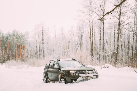 Renault Duster Or Dacia Duster Suv Parked In Snowdrift. Winter Snowy Forest. Duster Produced Jointly By French Manufacturer Renault And Its Romanian Subsidiary Dacia