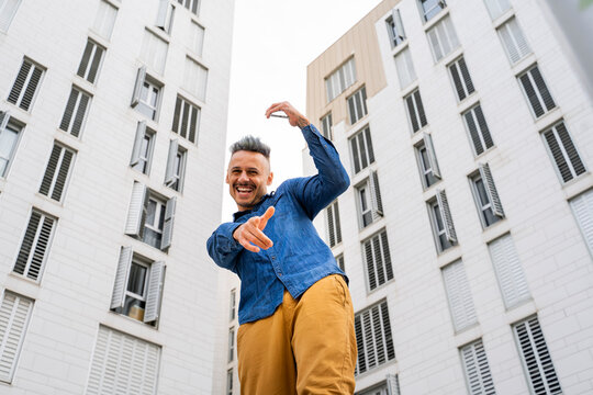 Cheerful man dancing against white buildings