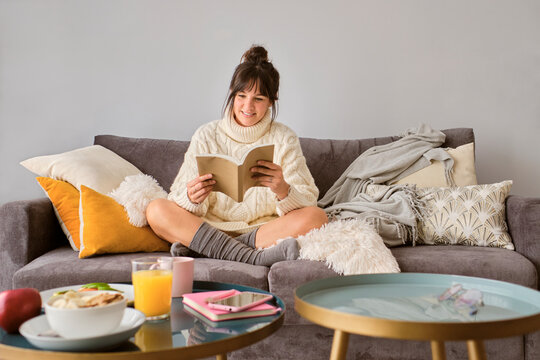 Smiling woman in sweater reading book while sitting on sofa at home