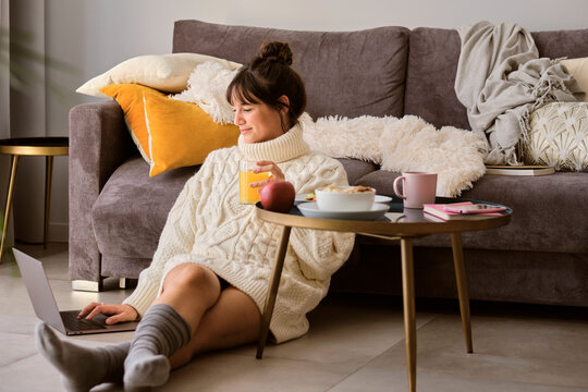 Woman in sweater having juice while using laptop at home