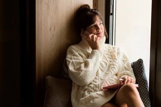 Beautiful woman in warm clothing looking through window while talking on mobile phone at home