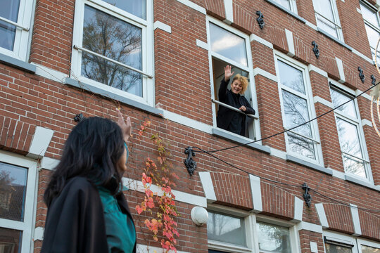 Young woman waving through window to female friend standing outside