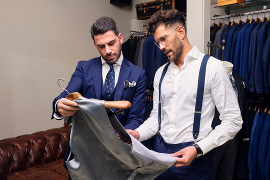Tailor and customer looking at gray waistcoat in tailors boutique