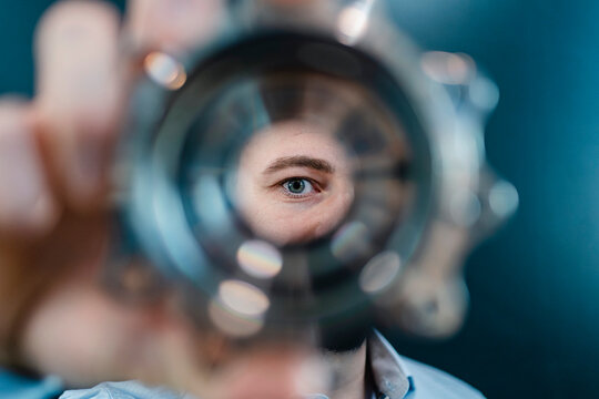Male professional's eyes seen through circular machine part in factory