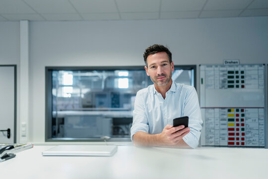 Male professional with mobile phone at desk in factory office