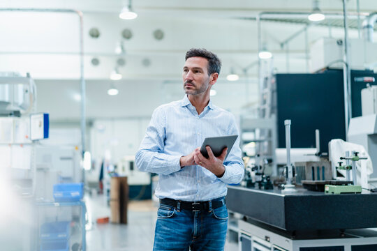 Businessman holding digital tablet while contemplating in industry