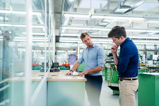 Male coworkers discussing over digital tablet on desk while working in factory