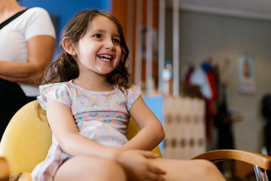 Cheerful cute girl sitting on chair at barber shop
