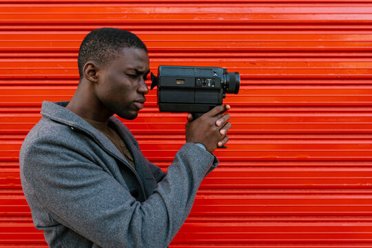 Man looking using 1980s film camera while standing against red wall