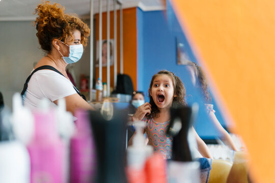Shocked girl shouting at female hairdresser seen from mirror reflection in hair salon