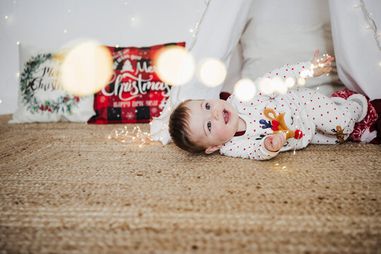 Baby girl playing with string light while lying on floor at home during Christmas