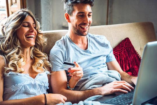 Laughing couple browsing laptop