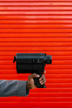Man holding 80's film camera against red wall