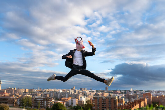 Businessman wearing pig mask jumping while taking selfie in city against sky