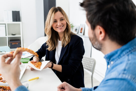 Business people eating pizza and talking in office during break