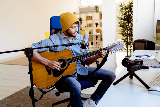 Musician playing guitar while streaming live through camera at recording studio