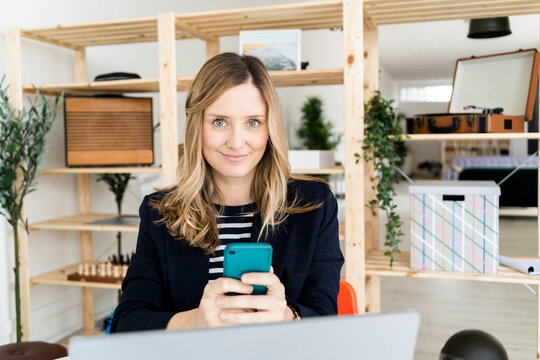 Portrait of smiling business woman using smart phone in office