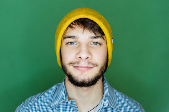 Young man staring while standing against green background