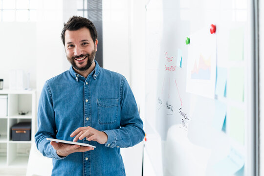 Portrait of smiling business man standing at whiteboard in office
