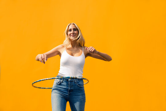 Young woman spinning hula hoop against wall wall
