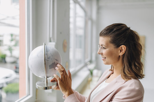 Smiling businesswoman touching globe in office